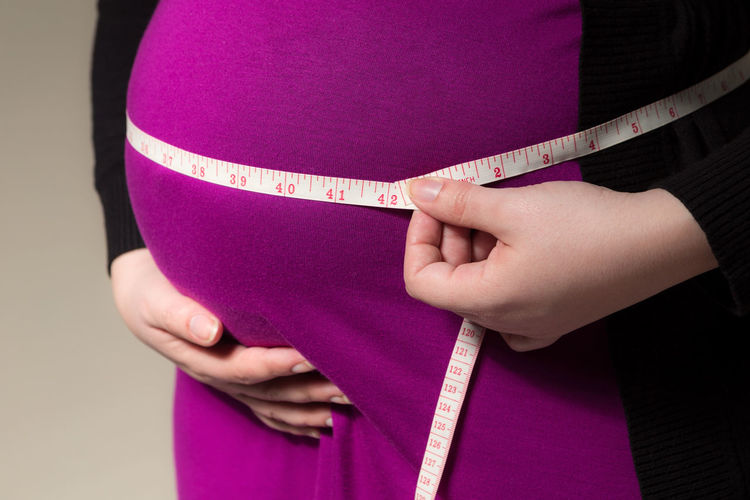 Midsection of pregnant woman with tape measure