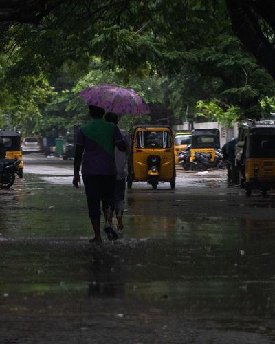 People walking on wet road in rainy season