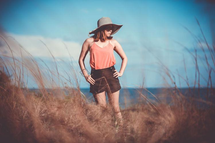 Woman wearing hat standing on field against sky