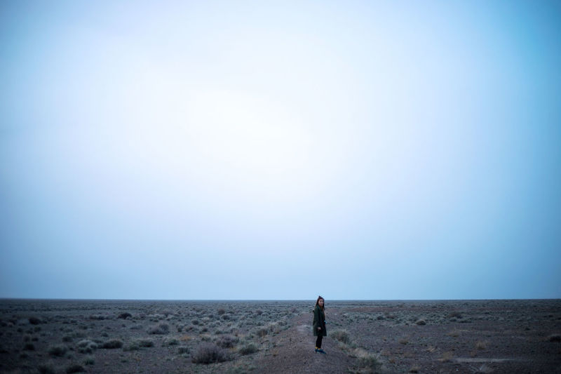 Rear view of man standing on field against clear sky