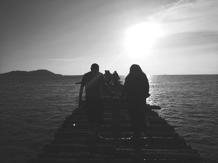 Silhouette people walking on pier over sea against sky during sunset