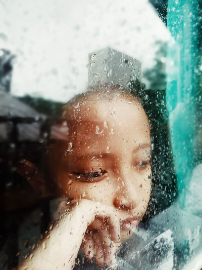 Portrait of woman seen through wet glass window