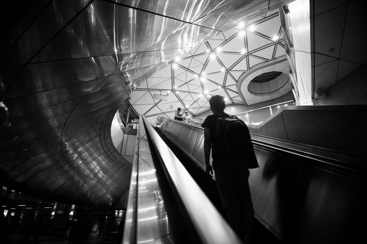 Architecture Blackandwhite Built Structure Conflict Escalator Futuristic Illuminated Indoors  Jealous Lifestyles Light And Shadow Men Modern Monochrome One Person People Real People Rear View Shadow Staircase Standing Steps Streetphotography Transportation Walking The Street Photographer - 2017 EyeEm Awards The Architect - 2017 EyeEm Awards The Architect - 2017 EyeEm Awards