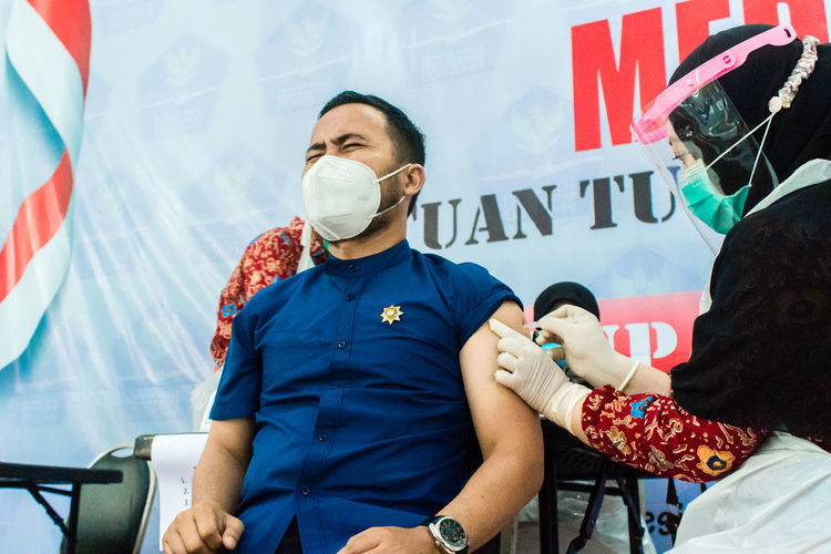 Man wearing mask getting vaccinated