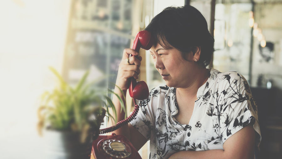 Thoughtful Woman Holding Telephone While Looking Away