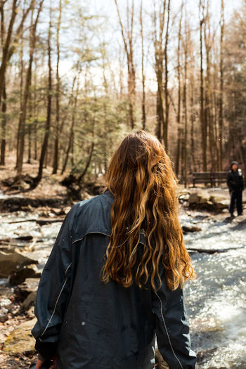 Rear view of woman standing by stream in forest