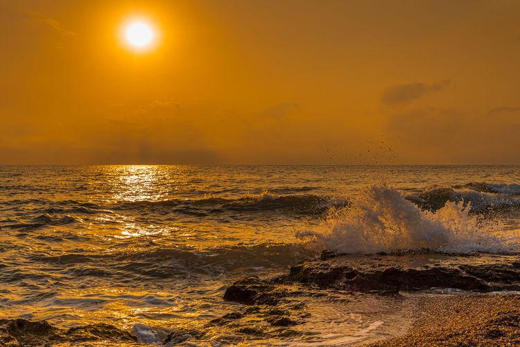 Sea Water Sky Sunset Scenics - Nature Horizon Beauty In Nature Horizon Over Water Wave Motion Orange Color Beach Land Nature No People Idyllic Power In Nature Splashing Sun Outdoors Breaking Seaside Dusk