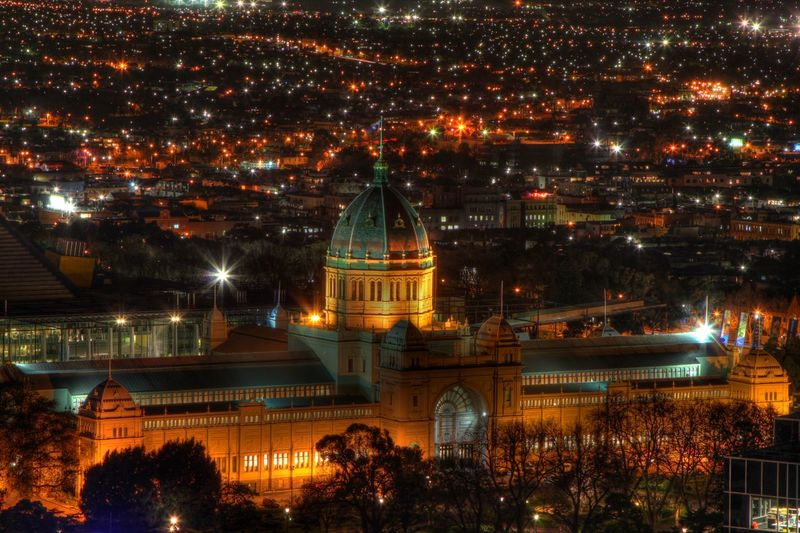 Illuminated royal exhibition building and cityscape at night