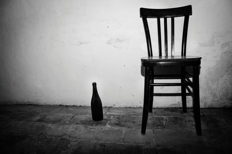 Chair and bottle on floor