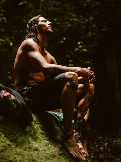 Man looking away while sitting on land
