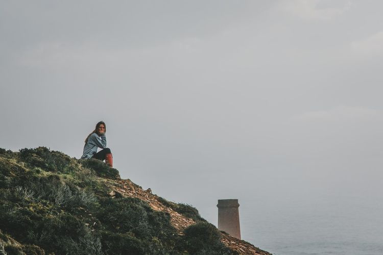Woman Sitting On Cliff Against Sky