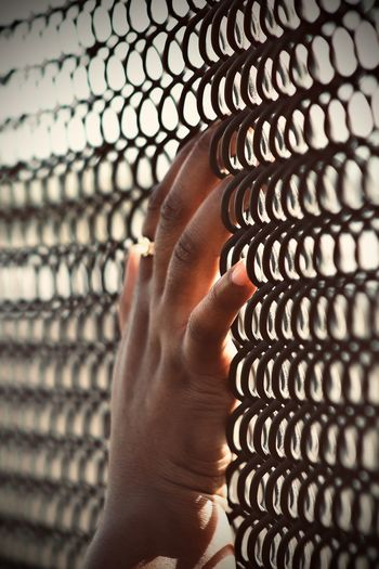 Close-up of person hand on metal fence