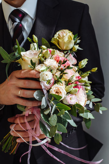 Cropped Hand Of Woman With Man Holding Rose Bouquet
