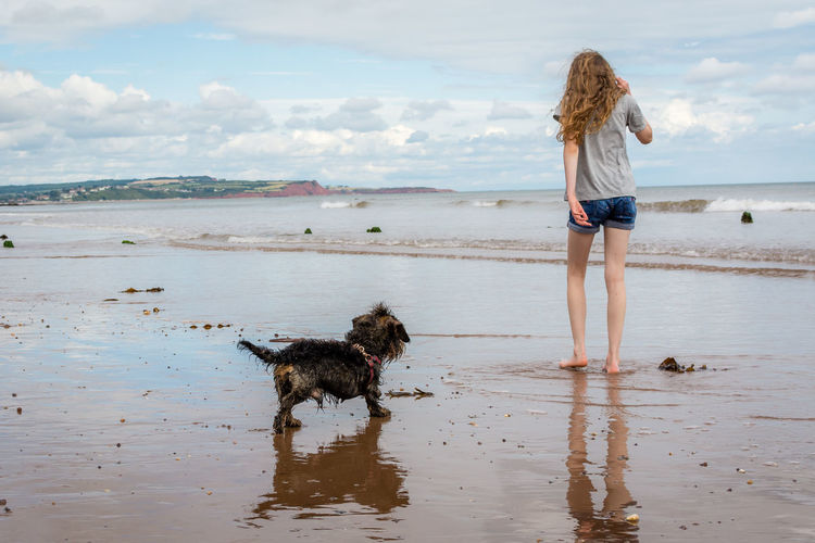 Woman with dog standing on beach