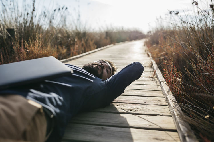 Man with laptop lying down amidst field on boardwalk during sunny day