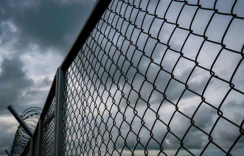 Low angle view of chainlink fence against sky
