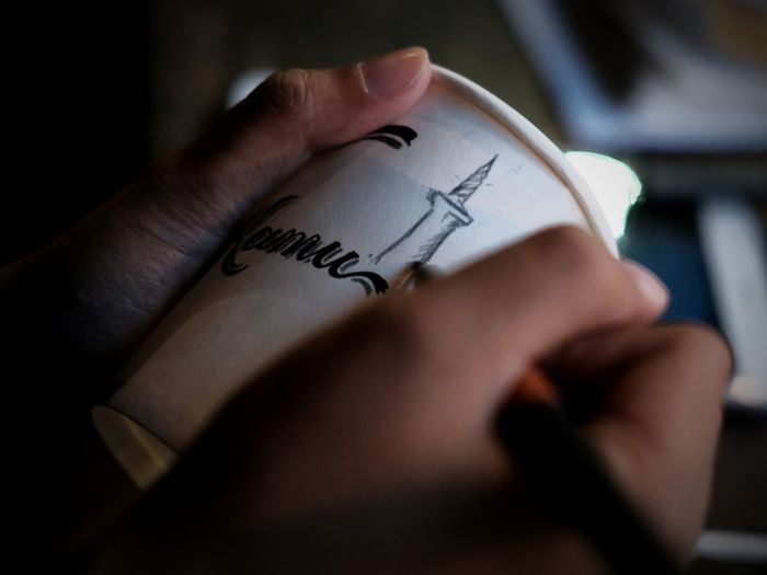 Cropped hand of woman writing on disposable cup