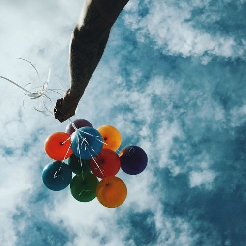 Cropped image of hand holding colorful balloons against sky