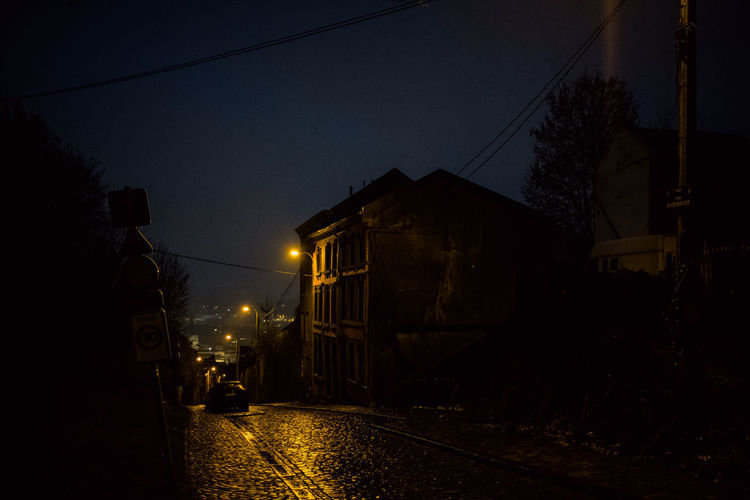 Rain Atmospheric Mood Eerie Night Building Exterior Architecture Illuminated Street Built Structure City Street Light Building Tree Sky Nature Residential District No People Mode Of Transportation Transportation Dark Plant Silhouette Cable Outdoors
