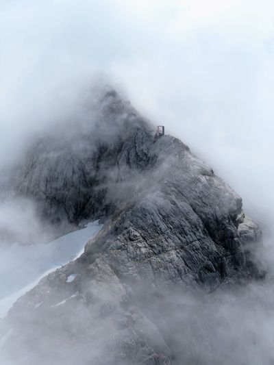 Scenic view of mountain amidst clouds