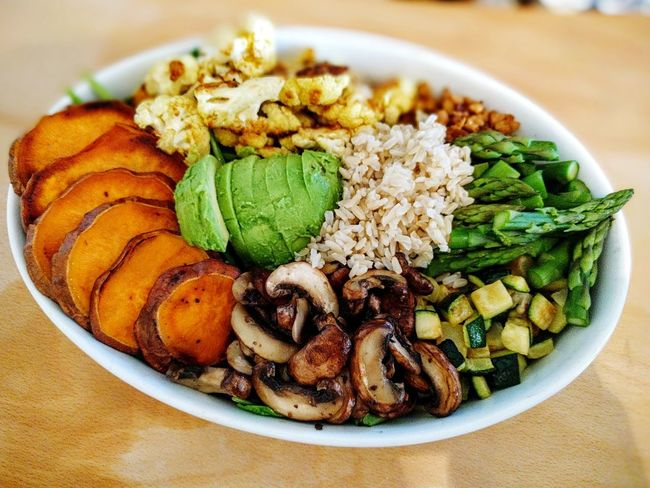 Awesome Buddhabowl with Spinach, Avocado, Cauliflower, Green Asparagus, Sweet Potatoes, Soy Flakes, Champignons & Zucchini.