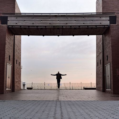 Full Length Of Silhouette Man Jumping Amidst Buildings At Battery Park