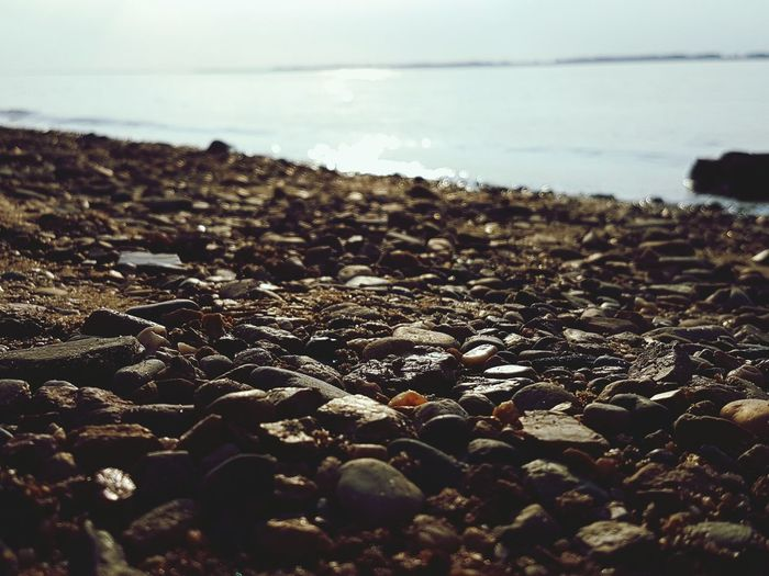 Close-up of pebbles with sea in background
