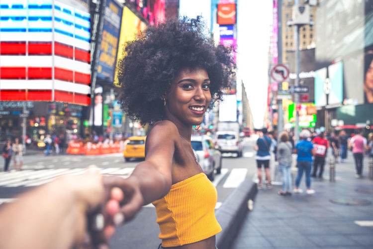 Side view portrait of happy young woman with afro hairstyle holding hand on city street