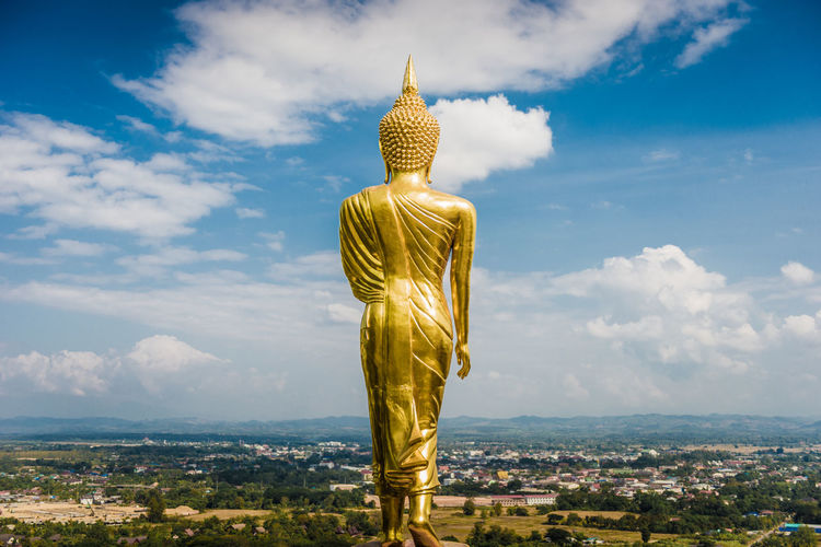 Behind of golden buddha statue that face toward to city, Thailand Art Belief Buddha Cloud - Sky Day Faith Gold Colored Golden Color Landmark No People Outdoors Peace Peaceful Religion Religious  Sky Sky And Clouds Spirituality Statue Statue Temple Thailand