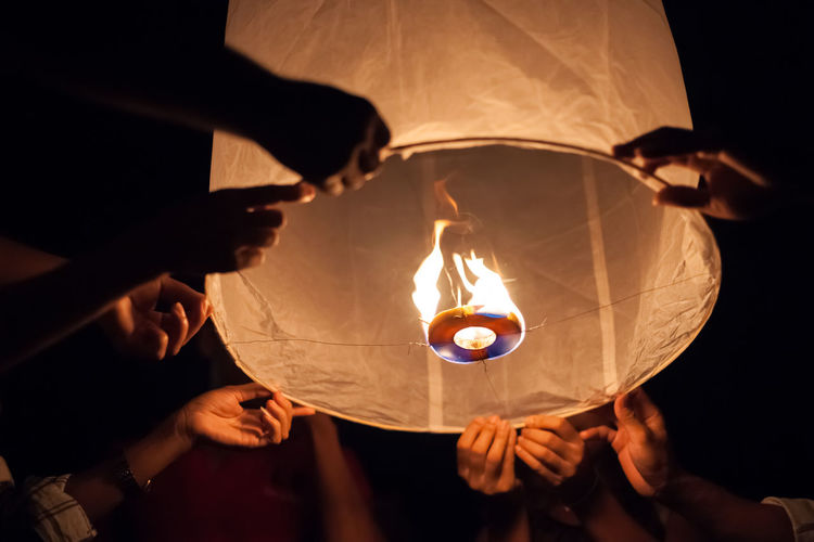 Cropped hands holding illuminated paper lantern