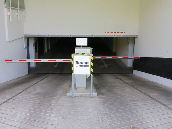 Entrance and driveway to an underground parking garage Architecture Barrier Building Built Structure Closed Copy Space Driveway Entrance Entrance Gate Locked No People Parking Parking Garage Parking Lot Protection Security Security Barrier Ticket Machine Underground Garage Underground Parking Urban Wall