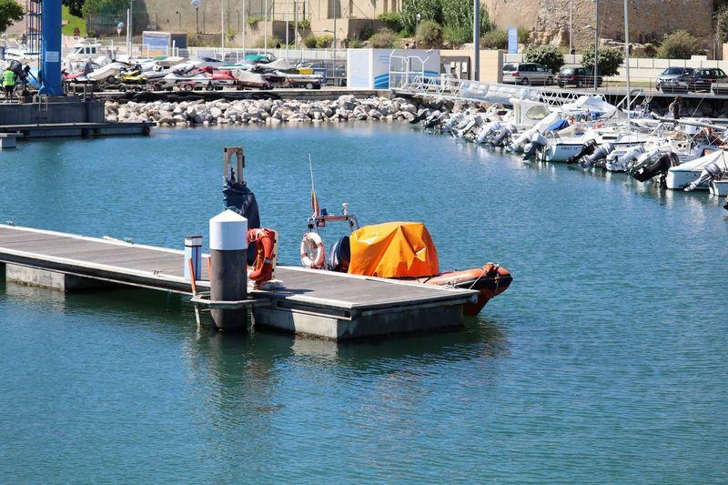 Speedboat moored by pier at harbor