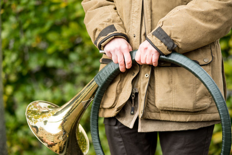 French horn band held in hands by a hunter on Saint Hubertus Day, 05/11/2017, De Moer, The Netherlands Brass Instrument  Green Color Hands Hunter Saint Hubertus Sound Tradition Chase Close-up Culture Day Fox Human Body Part Human Hand Hunting Hunting Horn Khaki Men Midsection Musical Instrument One Person Outdoors Real People Trumpet Trumpeter