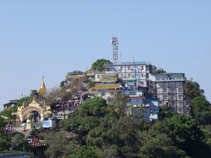 Mount Kyaiktiyo (Golden Rock) Pagoda Blue Sky Buddhist Pagoda Buddhist Temple Buildings Clear Sky Composition Distant View Evening Sunlight Golden Rock Pagoda Hillside Kinpun Mount Mount Kyaiktiyo Myanmar No People Outdoor Photography Place Of Pilgrimage Place Of Prayer Place Of Worship Religion Tourism Tourist Attraction  Tourist Destination Travel Destinations Trees