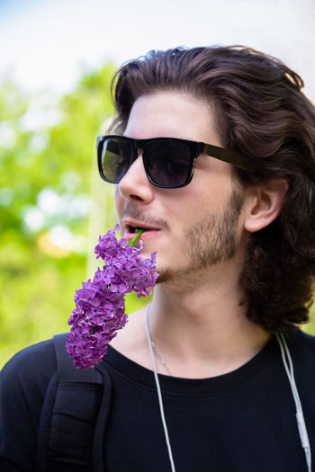 Young brunette guy smelling fresh flowers on lilac branch and looking at camera on blurred background Portrait Front View One Person Young Adult Leisure Activity Headshot Flowering Plant Flower Hairstyle Outdoors Purple Lilac Lilac Flower Smelling Smelling The Flowers Young Man Springtime Spring Brunette Handsome Handsome Boy Guy Park Branch Cute Curly Hair Glasses Sunglasses Young Men Fashion Real People Lifestyles Beard Day Close-up Facial Hair Human Face My Best Photo