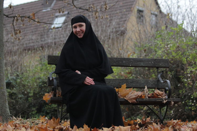 Orthodox nun, cover women is sitting on bench in november
