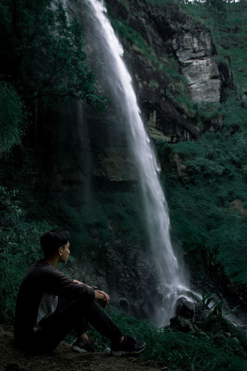 Side view of man sitting on rock in forest