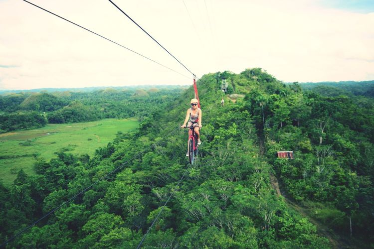 Woman Riding Bicycle On Zip Line Over Trees