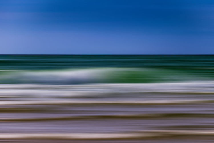 Blurred motion of sea against blue sky