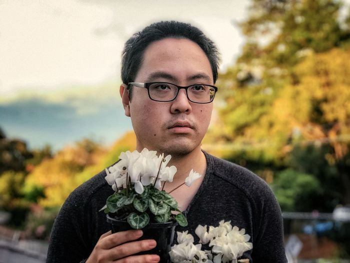 Portrait of young man holding potted white, flowering cyclamen plants against cloudy sky and trees.