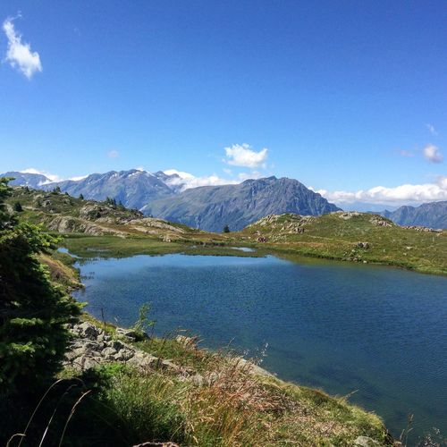 Scenic View Of Lake And Mountains Against Blue Sky At Huez