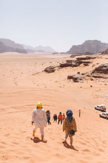 Rear view of people walking on desert