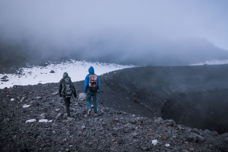 Finally we reached the intimidating crater of Tungurahua. Only a few meters more and then we'd reach the summit. Mountain Hiking Leisure Activity Nature Day Outdoors Adventure Remote Explore Discover  Crater Volcano Volcanic Landscape Snow High Altitude Clouds Fog Togetherness Walking Backpack Two People Warm Clothing Climbing Rear View Men