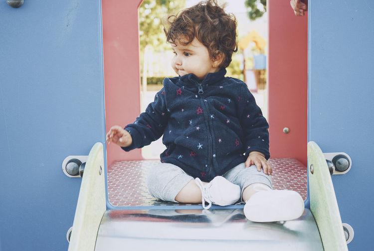 Boy sitting near slide in playground