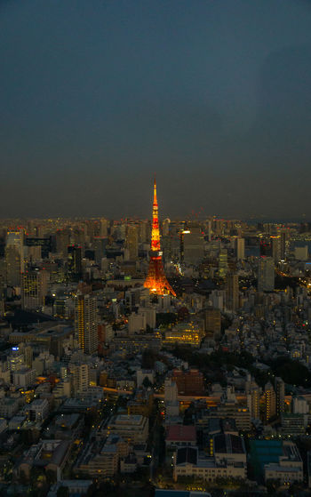 Aerial view of illuminated tokyo tower amidst cityscape against sky at night