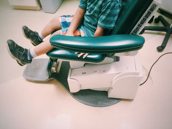 Low section of boy sitting on dentist chair