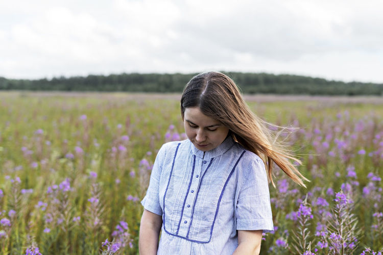 Young beautiful thoughtful blond woman in purple shirt walking in meadow among flowers of fireweed