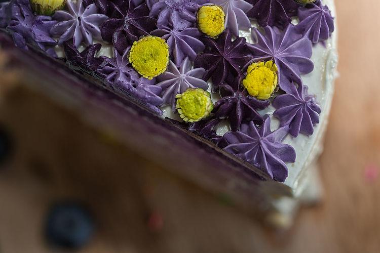 Purple cake with lemon buttercream is cut into mini individual cakes.