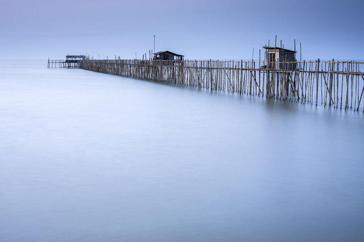 Stilt Houses And Pier Over Sea Against Clear Sky