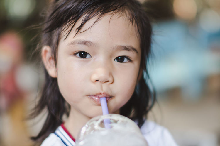 Childhood Portrait Child Headshot One Person Innocence Close-up Cute Real People Looking At Camera Front View Food And Drink Drinking Straw Holding Focus On Foreground Drink Refreshment Straw Lifestyles Drinking Temptation